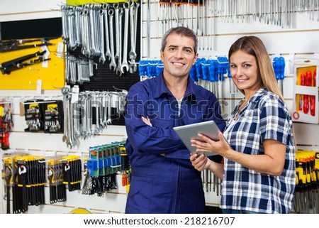 Portrait of female customer and male vendor with digital tablet in hardware store - stock photo