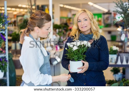 Portrait of female customer being assisted by salesgirl in buying flower plants at store - stock photo