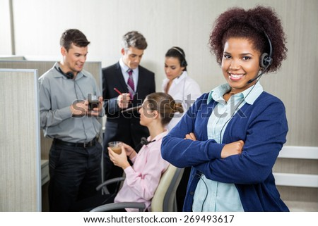 Portrait of female customer service representative standing arms crossed while team discussing in background at call center - stock photo