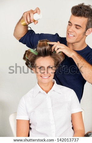 Portrait of female customer with hairstylist setting curls with hairspray in salon - stock photo