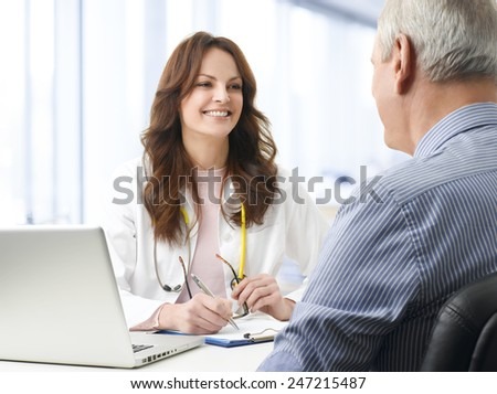 Portrait of female doctor consulting her old patient at hospital. - stock photo