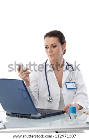 Portrait of female doctor sitting at desk at work, using laptop computer and mobile phone, smiling. - stock photo