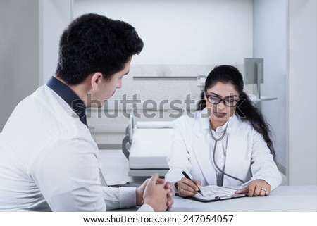 Portrait of female doctor writes an advice on the paper to her patient after checkup - stock photo