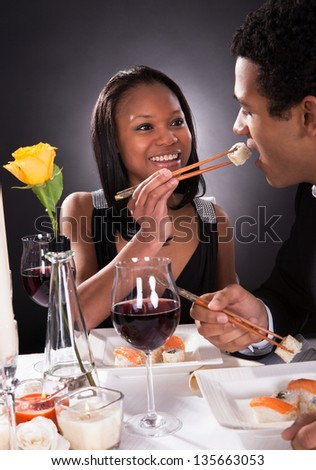 Portrait Of Female Feeding Sushi To Male At Dinner - stock photo