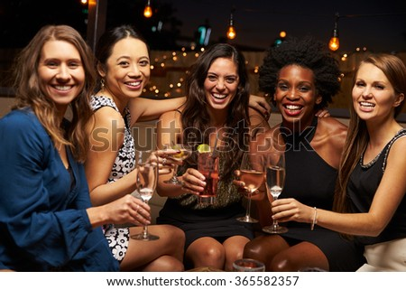 Portrait Of Female Friends Enjoying Night Out At Rooftop Bar - stock photo