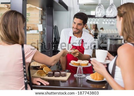 Portrait of female friends with male barista at counter in the coffee shop - stock photo