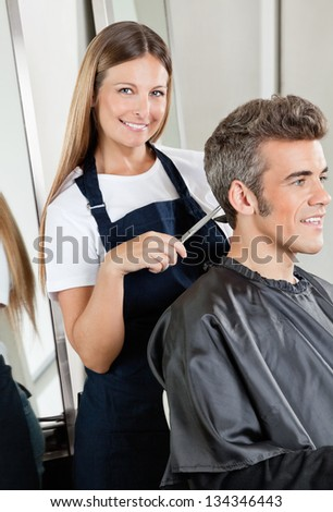 Portrait of female hairdresser cutting client's hair in salon - stock photo