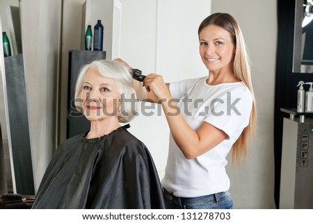 Portrait of female hairdresser ironing senior woman's hair in salon - stock photo