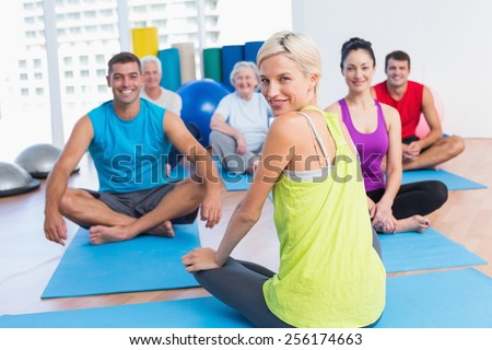 Portrait of female instructor with class practicing yoga in fitness studio - stock photo