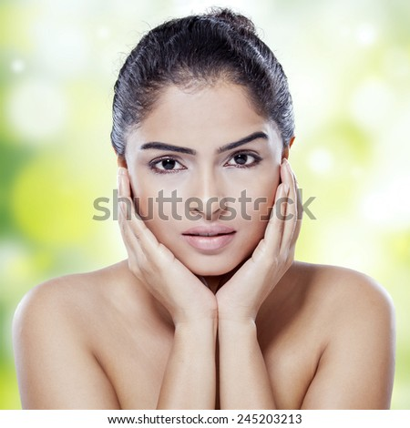 Portrait of female model with gorgeous face and perfect skin looking at camera against bokeh background - stock photo