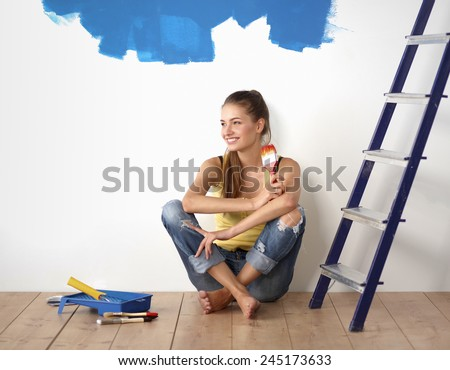 Portrait of female painter sitting on floor after painting. - stock photo