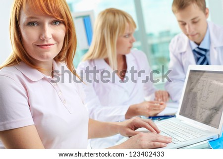 Portrait of female patient looking at camera while working with laptop - stock photo