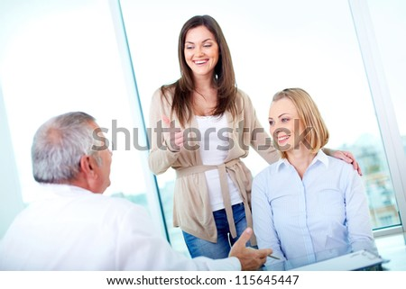 Portrait of female patient showing thimb up with her friend at medical consultation in hospital - stock photo