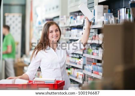Portrait of female pharmacist keeping a box on shelf - stock photo