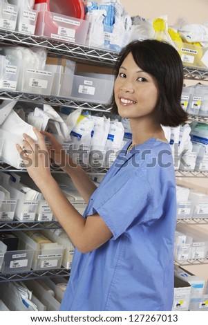 Portrait of female pharmacist standing by shelf at pharmacy - stock photo