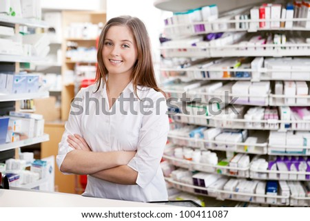 Portrait of female pharmacist standing with arms crossed at counter in pharmacy - stock photo