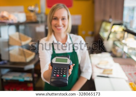 Portrait of female shop owner holding credit card reader in bakery - stock photo
