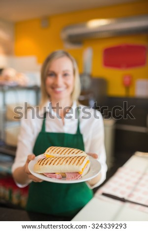 Portrait of female shop owner serving sandwich in plate - stock photo
