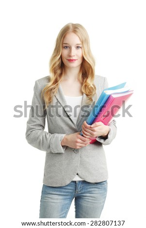 Portrait of female student holding files in her hands and standing against white background. - stock photo
