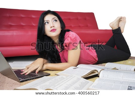 Portrait of female student lying on the carpet while daydreaming and studying with books and laptop computer - stock photo