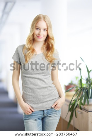 Portrait of female student standing at classroom while looking at camera and smiling. - stock photo