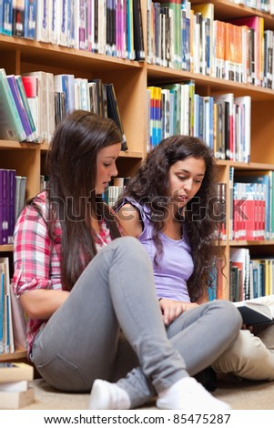 Portrait of female students reading a book in a library - stock photo