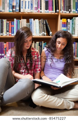Portrait of female students reading in a library - stock photo