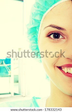 Portrait of female surgeon or nurse wearing protective uniform - stock photo