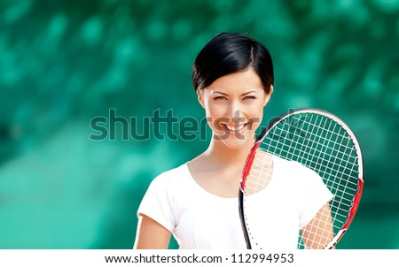 Portrait of female tennis player with racket at the tennis court. Outdoors - stock photo
