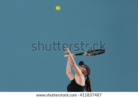 Portrait Of Female Tennis Player With Racket Ready To Serves Toss Ball - stock photo