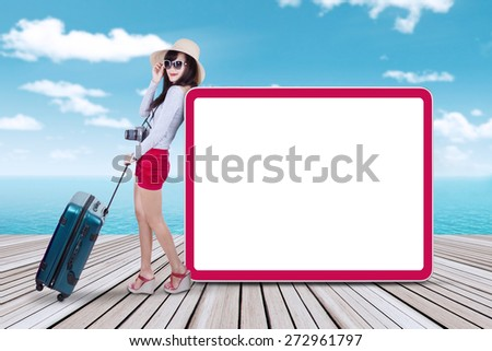 Portrait of female traveler standing at the pier near the empty billboard - stock photo