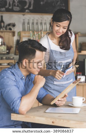 portrait of female waitress explain about the menu to her customer - stock photo