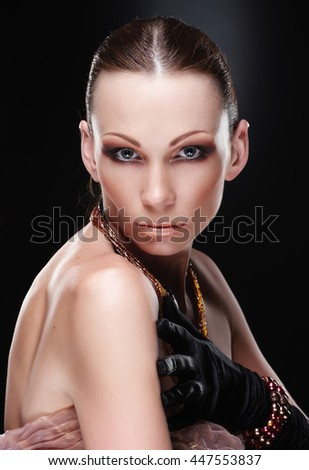 Portrait of female with evening make up on a dark background. - stock photo