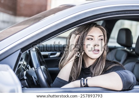 Portrait of female Young brunette dreaming and looking far away girl sitting in luxury black car Slim cute asian scary woman listening music inside black leather chair auto hand Fingers in long hair - stock photo