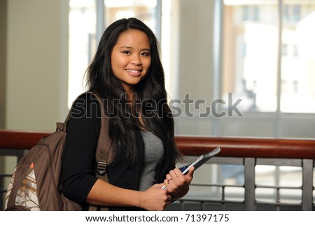 Portrait of Filipino girl with notebook and backpack indoors - stock photo