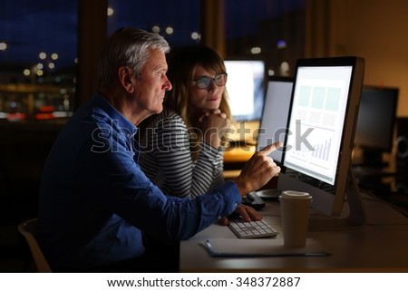 Portrait of financial team sitting at office and working late night. Managing director and professional businesswoman consulting while working on computer on financial project. Teamwork. - stock photo