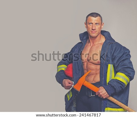 Portrait of fireman posing on grey background - stock photo