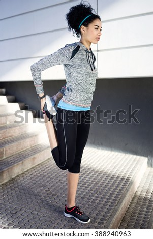 Portrait of fit and sporty young woman doing stretching in city. - stock photo
