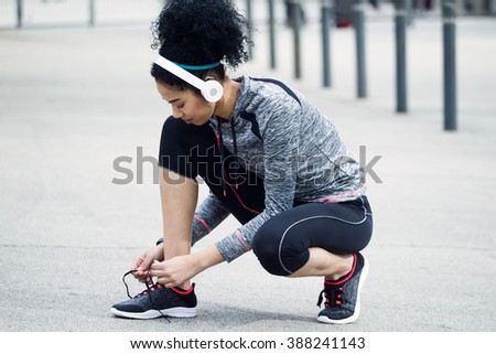 Portrait of fit and sporty young woman tying her laces before a run. - stock photo