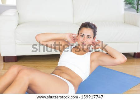 Portrait of fit calm woman doing sit ups on exercise mat in her living room - stock photo