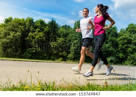 Portrait of fit Caucasian couple running outdoors - stock photo