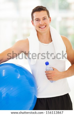 portrait of fit man holding water bottle and fitness ball - stock photo