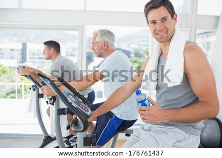 Portrait of fit man on exercise bike holding water bottle at gym - stock photo