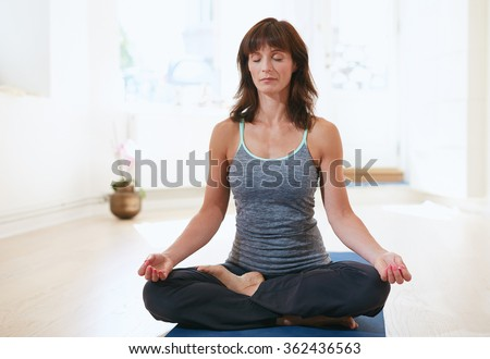 Portrait of fit mature woman in a meditative yoga pose at gym. Healthy female model doing padmasana at health club. - stock photo