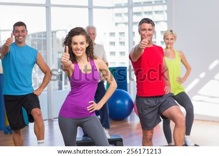 Portrait of fit people gesturing thumbs up in fitness class - stock photo