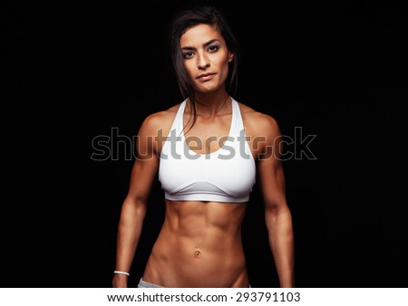 Portrait of fit young woman posing wearing sports bra against black background. Determined sportswoman in studio. - stock photo