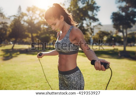 Portrait of fit young woman with jump rope in a park. Fitness female doing skipping workout outdoors on a sunny day. - stock photo