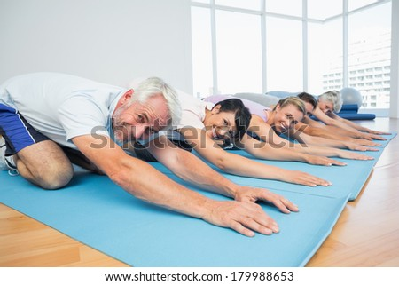 Portrait of fitness group bowing in row at the yoga class - stock photo