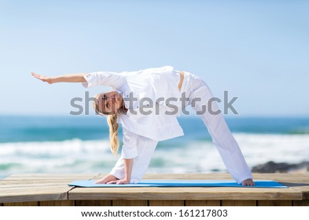 portrait of fitness senior woman exercising outdoors on beach - stock photo
