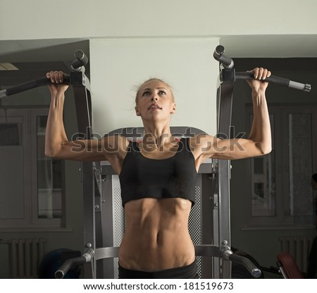 Portrait of Fitness Woman with smiling face. Close-up young adult blond girl with long hair holding simulator for swing press on dark green wall background - stock photo